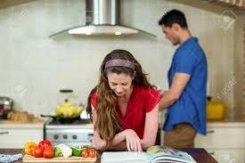 livre cuisine homme femme vérification le livre de recettes dans la cuisine tandis que