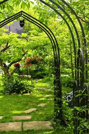 lush green garden with wrought iron arbor stock photo picture and