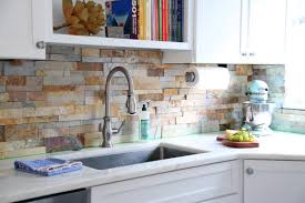stacked stone backsplash on new modern kitchen detail sink marble