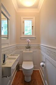 bathroom vanity with wainscoting and beige tile also bathroom