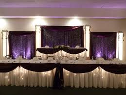 head table backdrop with crystals and purple uplights cc events