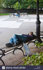 homeless teenager sleeping on a park bench in brooklyn new york