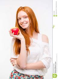 beautiful happy with long red hair holding an apple stock