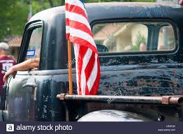 Car Window Flags An American Flag Is Attached To The Back Of An Old Beat Up Pickup