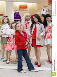 Little Girls Clothing Stores Little Girls Trying On Red Clothes Together With Mannequins