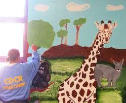 children greeted by inmate painted murals at high desert state