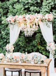 wedding arch with fabric and chandelier sweetheart table flowers