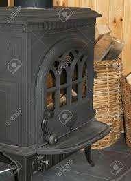 an old black cast iron fireplace with baskets of firewood next