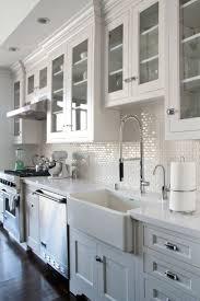 white kitchen cabinets glass doors dark wood floors backsplash