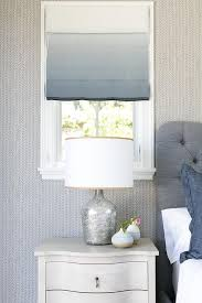 gray and blue bedroom with curved gray nightstands and mercury