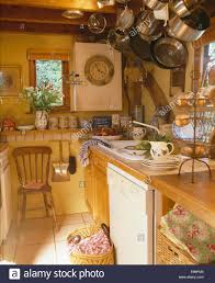 Cottage Kitchen by Stainless Steel Pans On Hanging Storage Rack In Small Cottage