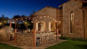stone outdoor kitchen pizza oven and patio with lights an
