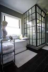 stylish bathroom with framed black shower stall and freestanding