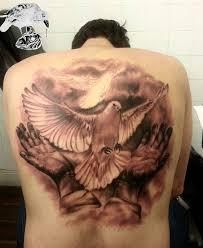 realistic hands and dove tattoo idea on back golfian com