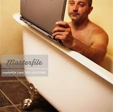 laptop bathtub man using laptop computer in bathtub stock photo masterfile