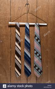 retro wood paneling three retro ties hanging on a wire hanger against wood paneling