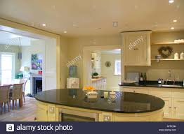 modern cream kitchen black granite worktop on oval island unit in modern cream kitchen