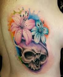 beautiful watercolor lily flower and skull tattoo on side rib