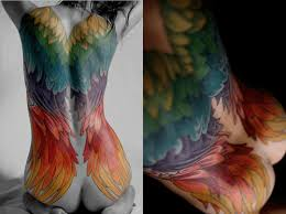 a full back tattoo on a woman that shows angel wings in a
