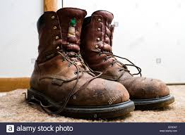 used motorcycle boots a pair of well used work boots sitting by the door stock photo