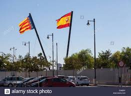 giant flags of spain and the valencian community fly in the port