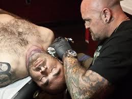 an awkward photo of shirtless aaron lewis getting tattoos