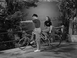 Fake Shrubs Richard Greene And Vera Zorina Ride Bikes And Point To Something