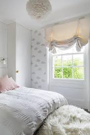 white and pink bedroom with white feather chandelier