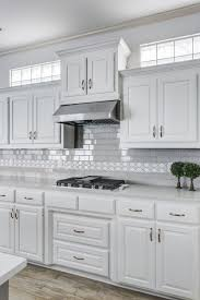grey and white kitchen white cabinets with grey subway tile and a