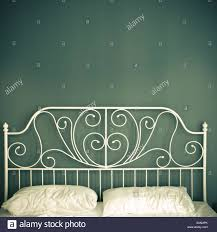white cast iron bed head crumpled pillows green wall stock photo