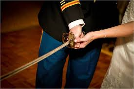 and military groom cut wedding cake with large military sword