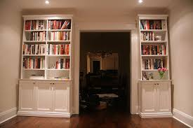 high white wooden books shelves having storage under it with door