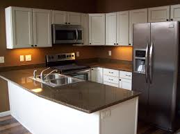 gold brow marble countertops on white kitchen cabinets with u