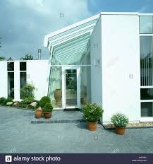 modern house porch paving in front of modern white house with glass porch stock photo