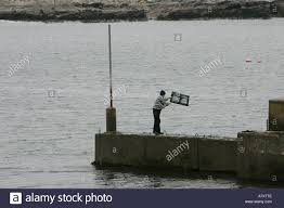men throwing a lobster pot into the sea from downings pier county