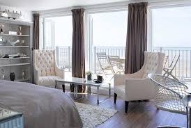 Ralph Lauren style white bedroom overlooking with balcony the beach