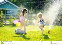 girls running though a sprinkler in a backyard stock photo image