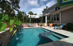 pool with spa and a stone wall with waterfalls aqua blue pools