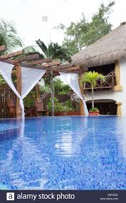 view of villa in tulum mexico with blue swimming pool and cabana
