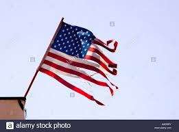 Ripped American Flag Tattered And Torn American Flag Blows In Strong Wind Stock Photo