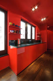 chic red kitchen cabinets added black tiled countertops as well as
