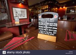 a small chalkboard menu on a table in the bar of the fiddler u0027s