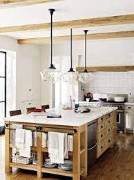 Rustic Kitchen Island Light Fixtures by Two Goodman Hanging Lamps In Antique Brass Stands Over A White