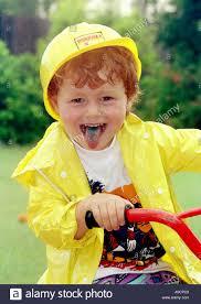 bike raincoat a young boy riding a bike in the rain wearing a yellow raincoat