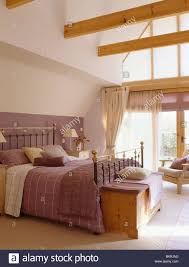wooden chest below antique brass bed with mauve bed linen in large