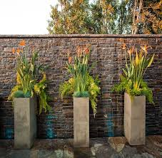 striking tall container arrangements to adorn a brick wall out