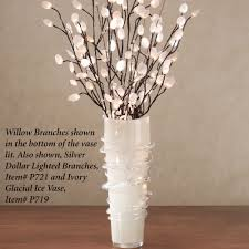 decorating huge white lighted branches with glass vase for