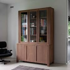 large bookshelf with three glass and wooden doors upper and lower