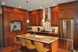 brown cherry wood kitchen cabinet and island with white pictures