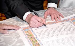 Being a Guest at a Jewish Wedding  A Guide   My Jewish Learning My Jewish Learning Bride and groom signing a katuba in front of a Rabbi during their wedding ceremony